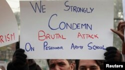 A member of the civil society hold placard and chant slogans to condemn the attack on the Army Public School by Pakistan Taliban gunmen, during a rally with others in Lahore, Dec. 18, 2014.