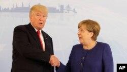 Nan Somè G20 yo, Prezidan ameriken an, Donald Trump, agoch, ak Chanselye almand lan, Angela Merkel nan Hamburg, Almay, 6 jiyè 2017.