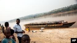 Quelques personnes à côté d'un bateau vide, sur le bord de la rivière Kasaï, au port de Tshikapa, en République démocratique du Congo, le 28 juillet 2017.