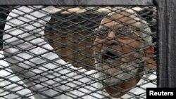 穆罕默德·巴迪在与其他穆兄会成员一道出庭受审时隔着被告囚笼呼喊口号。(2013年12月11日资料照)