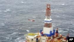 Dari foto yang dirilis oleh Pengawas Pantai Amerika ini, nampak sebuah helikopter dari pangkalan Kodiak tengah memberikan instruksi kepada 18 awak anjungan nomor 13 pengeboran minyak Kulluk (29/12). Anjungan milik perusahaan minyak Shell ini terlepas dari kapal yang menanganinya di laut yang berombak besar Teluk Alaska pada Malam Tahun Baru, dan kandas di pantai berbatu-batu pulau Sitkalidak.