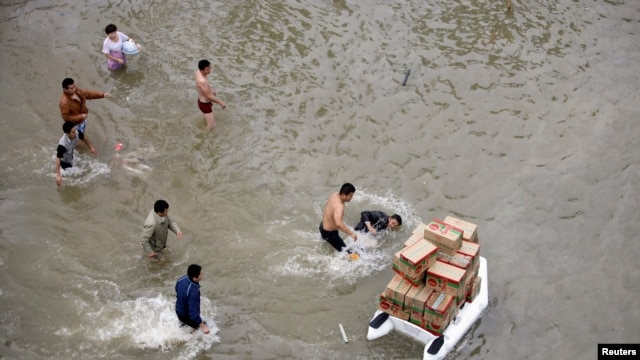 FILE - A volunteer (R) transporting boxes of food supplies on an inflatable raft, falls into the water after being pushed by a man (2nd R) as other people look on, on a flooded street during a supply shortage after Typhoon Fitow hit Yuyao, October 9, 2013.