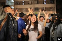 Pro-democracy supporters celebrate after pro-Beijing politician Junius Ho lost his election in Hong Kong, early Monday, Nov. 25, 2019.