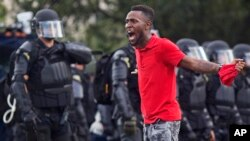 FILE - A protester yells at police in front of the Baton Rouge Police Department headquarters after police arrived in riot gear to clear protesters from the street in Baton Rouge, Louisiana, July 9, 2016.