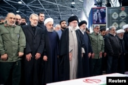 Iran's Supreme Leader Ayatollah Ali Khamenei and Iranian President Hassan Rouhani pray near the coffin of Iranian Major-General Qassem Soleimani, head of the elite Quds Force, who was killed in an air strike at Baghdad airport, in Tehran, Iran,