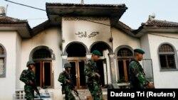 Tentara berjalan melewati masjid milik Ahmadiyah yang terbakar, di Ciampea, Jawa Barat, 2 Oktober 2010. Komnas HAM meminta polisi mengusut aktor intelektual perusakan rumah ibadah Jemaat Ahmadiyah Indonesia di Sintang, Kalbar (REUTERS/Dadang Tri)