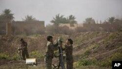 U.S.-backed Syrian Democratic Forces (SDF) هێزهكانی سوریای دێمۆكرات له كاتی ئامادهكردنی خۆمپاره بۆ نێو سهنگهرهكانی داعش له باغۆز، ١٣ی مارسی ٢٠١٩ی زاینی.