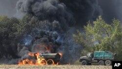 Vehículos militares sin insignias se incendian en una carretera en el este de Ucrania, cerca de Mariupol.