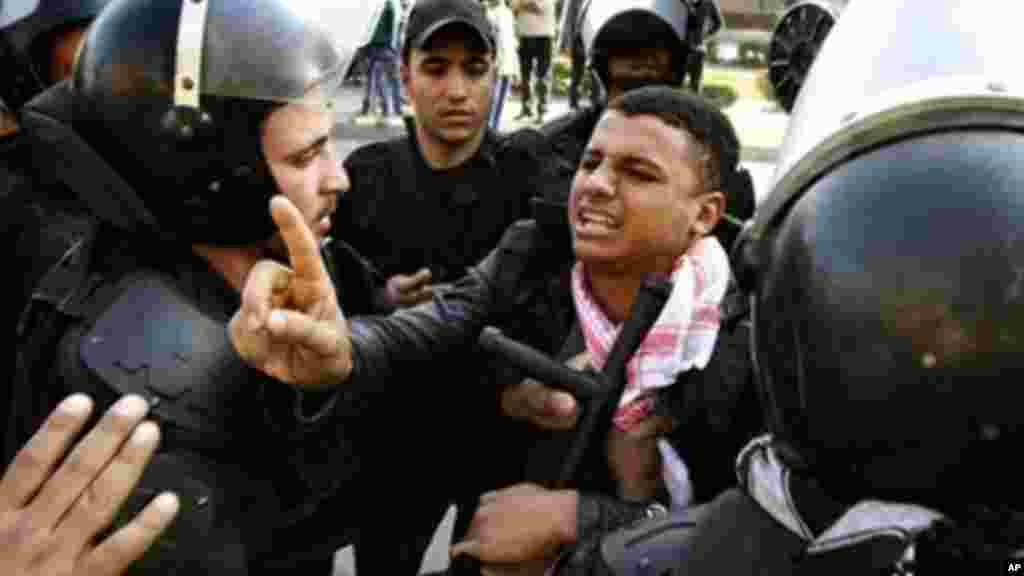 Egyptian riot police detain a man during clashes with supporters of ousted President Mohamed Morsi Cairo, Egypt, January 10, 2014.