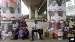 People sits under campaign posters of Lagos State Governorship candidate of the All Progressives Congress party, Akinwunmi Ambode, on the street in Lagos, Nigeria, April 10, 2015.