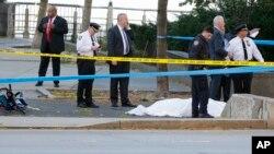 警方在出事现场调查。一名受难者遗体被蒙上白布。