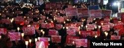 박근혜 한국 대통령이 3차 담화문을 발표한 29일 밤 서울 파이낸스 빌딩 앞에서 박 대통령의 퇴진을 주장하는 철도노조 조합원들과 시민들이 촛불집회를 열고 대통령 퇴진 구호를 외치고 있다.