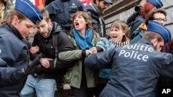 Polisi menahan sekelompok orang di Place de la Bourse di Brussels, Belgia (2/4). (AP/Geert Vanden Wijngaert)