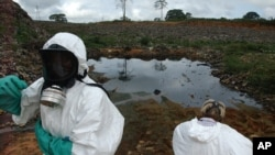 FILE - Waste removal experts work to remove hazardous black sludge from a garbage dump in Abidjan, Ivory Coast, Sept. 17, 2006. Many victims have still not received compensation.