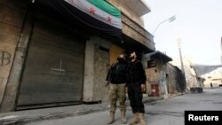FILE - Free Syrian Army fighters look at a Syrian opposition flag in Aleppo's Bustan al-Basha district.