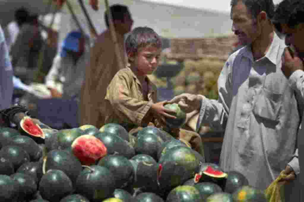 Un niño paquistaní vende sandías en el mercado de frutas y hortalizas en Islamabad, Pakistán.