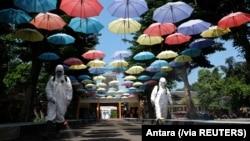 Para pekerja menyemprotkan cairan disinfektan untuk mencegah penularan virus corona (Covid-19) di Solo, Jawa Tengah, 18 Juni 2020. (Foto: Antara via Reuters)