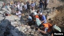 Abanya Palestina bariko barondera abantu boba bari mu bisigarira vy'inzu yasenyuwe na bombe yatewe n'indege y'ingwano y'igihugu ca Israel.