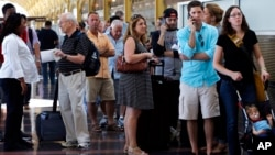 People stand in line at Washington's Reagan National Airport after technical issues at a Federal Aviation Administration center in Virginia caused delays, Aug. 15, 2015.