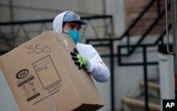 Seorang pekerja mengangkat box saat membersihkan asrama kampus (AP Photo/David Zalubowski)