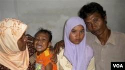 Meri Yulanda alias 'Wati' (15 tahun) bersama keluarganya: ayahnya, Yusuf (kanan), ibunya, Yusniar (kiri) dan adiknya Aris di rumahnya di Meulaboh, Aceh (23/12).