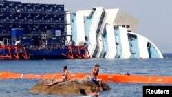 Bañistas se divierten frente a los restos del Costa Concordia, al que se le sumergido rodeado por grúas.
