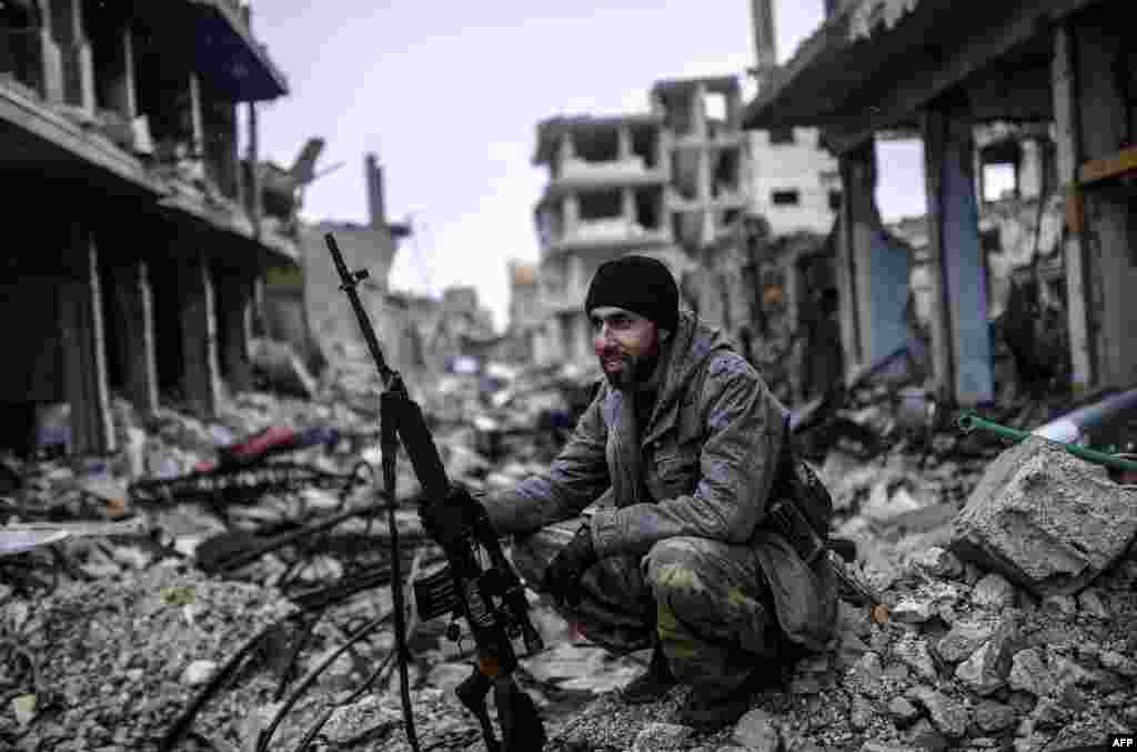 Musa, a 25-year-old Kurdish marksman, sits in the rubble of the Syrian town of Kobani, also known as Ain al-Arab. Kurdish forces recaptured the town on the Turkish frontier on January 26, in a symbolic blow to the jihadists who have seized large swaths of territory in their onslaught across Syria and Iraq.