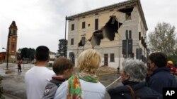 Warga tengah mengamati bangunan balai kota St.Agostino yang rusak akibat gempa (20/5). Gempa berkekuatan 6.0 mengguncang sekitar wilayah Bologna, menewaskan sedikitnya empat orang dan merusakkan bangunan serta rumah tinggal penduduk setempat.