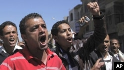 Anti-government protester shout slogans during a demonstration in Sanaa, February 15, 2011
