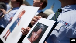 FILE - Fathers who lost their children to spousal abduction to Japan hold photos of their children during a news conference on Capitol Hill in Washington, May 5, 2010.