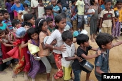 FILE - Rohingya refugee children push each other while waiting outside of an aid distribution center to receive aid supplies in the Palong Khali refugee camp in Cox's Bazar, Bangladesh, Nov. 15, 2017.