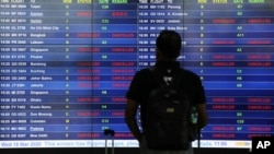 A man looks at an information board displaying cancelled flights after Malaysia's government closed its borders due to the spread of the coronavirus disease (COVID-19), at Kuala Lumpur International Airport in Sepang, Malaysia March 18, 2020. REUTERS/Lim