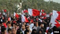 Demonstran anti-pemerintah berbaris dalam aksi protes di Riffa, Bahrain, Jumat (11/3), di mana polisi membentuk barikade untuk mencegah puluhan ribu demonstran bergerak menuju halaman istana kerajaan.
