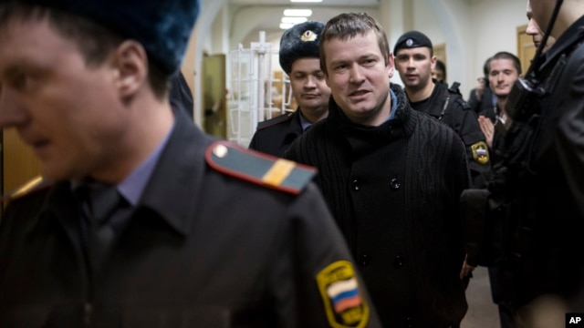 FILE - Russian opposition activist Leonid Razvozzhayev is escorted into a court room in Moscow, Russia,  April 1, 2013. Amnesty International says he was abducted by Russian state security agents operating in Ukraine.