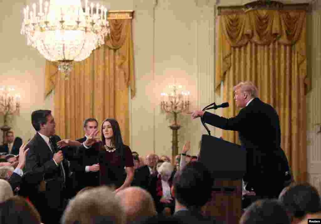 A White House staff member reaches for the microphone held by CNN's Jim Acosta as he questions President Donald Trump during a news conference following Tuesday's midterm U.S. congressional elections at the White House in Washington.