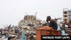 Un survivant est assis parmi les débris laissés par l'explosion la veille au quartier de Mpila à Brazzaville, le 5 mars 2012. (Photo: Patrick Fort /AFP)