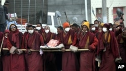 Tibetan monks carry the body of a quake victim during a funeral procession in Jiegu, Yushu county, in China's northwestern province of Qinghai on April 21, 2010.