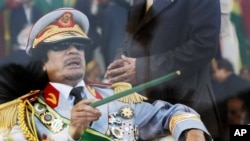FILE - Libyan leader Moammar Gadhafi gestures with a green cane as he takes his seat behind bulletproof glass for a military parade in Green Square, Tripoli, Libya.