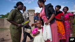 Christian women and children are scanned with a metal detector and have their bags searched to prevent against possible attacks, as they enter the compound of the Our Lady of Consolation Church in Garissa, Kenya, April 5, 2015.