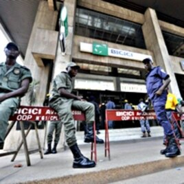 Security contain clients standing outside the headquarters of the Bicici bank as they came to withdraw money in Abidjan, March 3, 2011