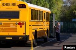 Seorang karyawan menunggu untuk membantu seorang siswa turun dari bus saat pembelajaran langsung dilanjutkan dengan pembatasan untuk mencegah penyebaran Covid-19) di Sekolah Dasar Rover di Tempe, Arizona, AS, 17 Agustus 2020. (Foto: Reuters)