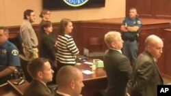In this image made from Colorado Judicial Department video, Defendant James Holmes, top left in tan shirt, defense attorneys, top left, and prosecuting attorneys watch as the jury exits the courtroom after delivering their sentencing verdict in the Colora