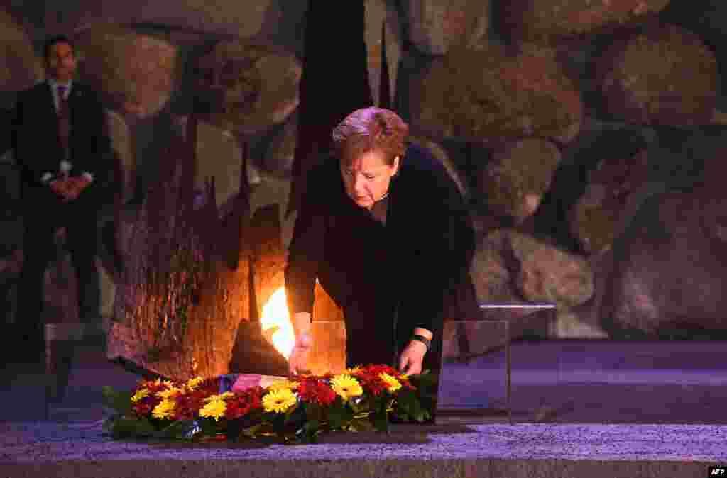 អធិការបតីអាល្លឺម៉ង់ លោកស្រីAngela Merkel ដាក់កម្រងផ្កានៅមុខគំនូរស្តីពីការចងចាំសង្គ្រាមលោកលើកទី១ នៅសារមន្ទីរYad Vashem Holocaust ក្នុងទីក្រុងហ្ស៊េរុយសាឡិម ប្រទេសអ៊ីស្រាអែល។