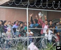 Migrantes centroamericanos detenidos en la frontera luego de cruzar ilegalmente a EE.UU., esperan debajo de un puente en el Paso, Texas, en un recinto cerrado instalado por la Patrulla Fronteriza debido a la falta de instalaciones para albergarlos. Marzo 27 de 2019.
