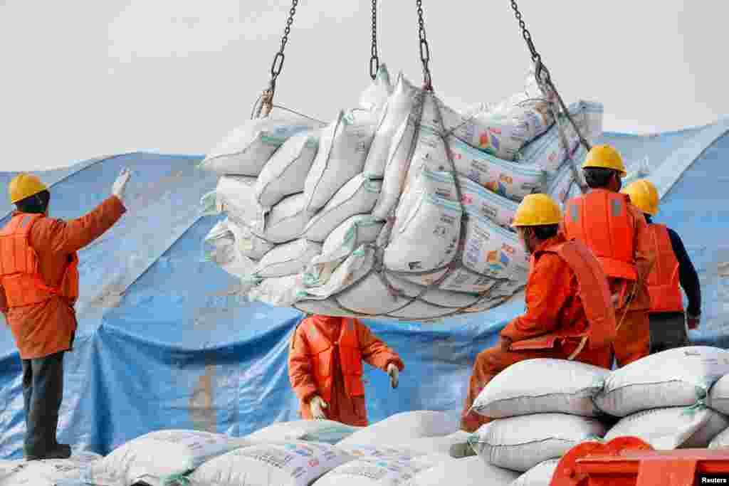 """2018年3月22日,中国江苏省南通港口工人装卸进口的大豆产品。香港东方日报的东网9月5日报道,以大豆加工为主要业务的中国九三粮油工业集团早前接受访问,其副董事长郭彦超预计:""""中国大豆的库存量将于今年11月降至最低位、到时大豆价格会非常高。到明年2月至3月,所有库存或将耗尽。""""报道引述他的话说,巴西大豆供应量有限,不能媲美美国,因此中国可能面临""""大豆危机""""。"""