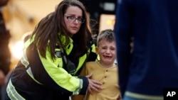 Pripadnica službi za hitne reakcije odvodi učenika u autobus u centru za rekreaciju gde su dovedeni roditeljima nakon pucnjave u školi Hajlends rač u Denveru, Kolorado, 7. maja 2019.