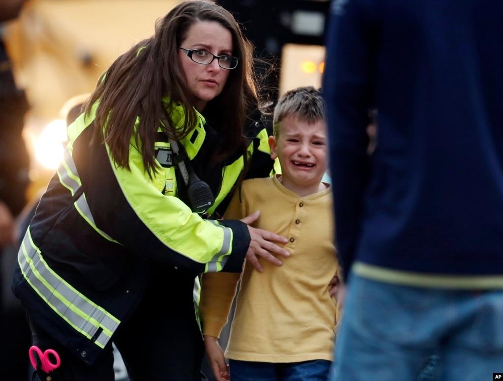 미국 콜로라도 주 덴버 교외 하이랜드 랜치 스템스쿨에서 총격 사건 현장을 벗어난 아이가 경찰의 인도를 받으며 울고 있다. 이번 총격 사건으로 인해 1명이 사망하고 8명이 다쳤다.