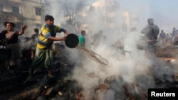 Seorang warga setempat mencoba memadamkan api di daerah kumuh di Kolkata, India (26/2). Ratusa warga kehilangan tempat tinggal dan sedikitnya 18 orang dikabarkan tewas dalam insiden tersebut. (REUTERS/Rupak De Chowdhuri).