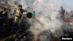 Cư dân địa phương cố gắng dập tắt đám cháy tại khu ổ chuột ở Kolkata, ngày 26/2/2013.
