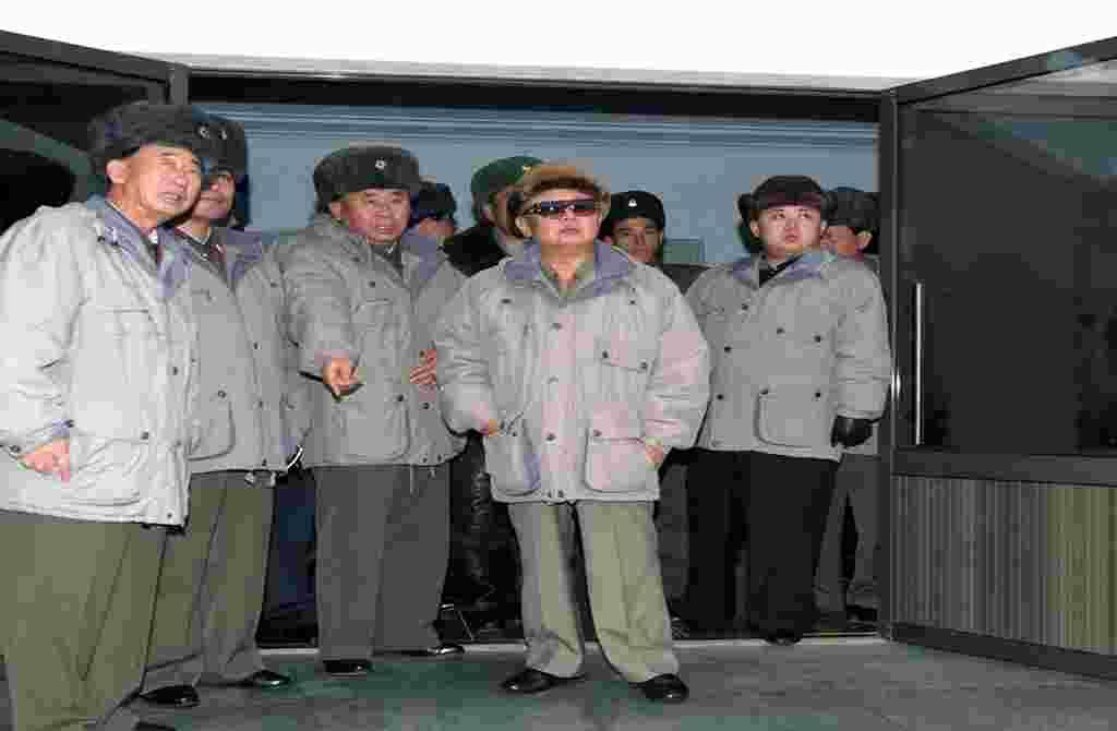 Dalam foto tanpa tanggal ini, terlihat Kim Jong Il (tengah) ditemani oleh putranya Kim Jong Un (kanan), mengunjungi Unit 1016 Angkatan Udara Korea Utara di sebuah lokasi yang tidak diketahui (foto: AFP).